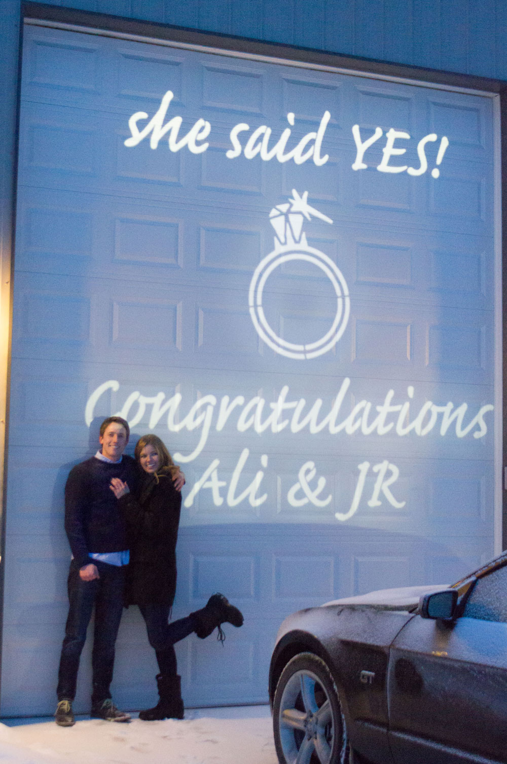Alexis and Jr beside a projected gobo that read 'She Said Yes Congratulations Ali and Jr'